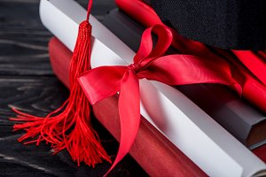 Graduation hat and diploma with red