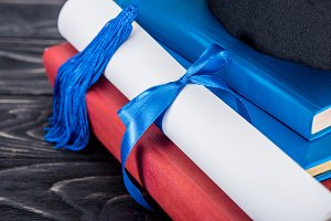 Graduation hat and diploma with blue