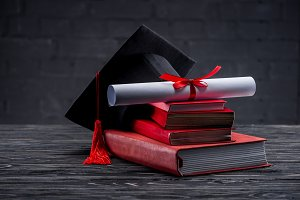 Stack of books with diploma and grad
