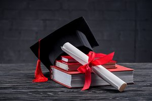Stacked books with diploma and gradu