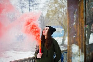 Young girl with red colored smoke bo