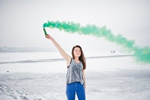 Young girl with green colored smoke