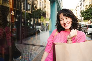 Cheerful shopping woman holding a pa