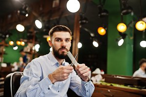 Handsome bearded man barber sitting