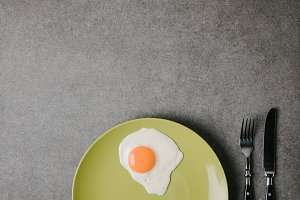 top view of fresh fried egg on plate
