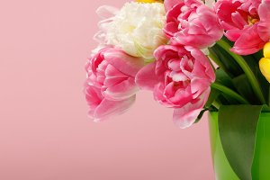 Bouquet of tulips in vase on pink ba