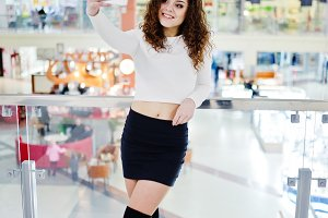 Young curly model girl making selfie