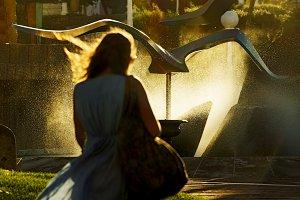 woman walking towards a fountain