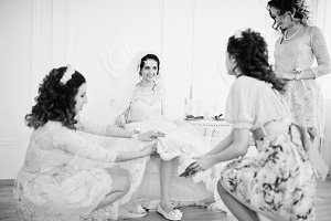 Bridesmaids helping bride to put her