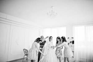 Bridesmaids and mother helping bride