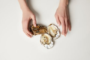 Female hands with fresh oysters on w