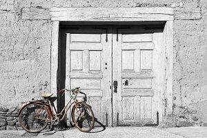 old vintage red bike on mud house