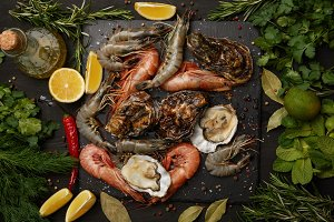 Shrimps and oysters on slate board w