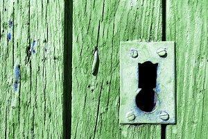 old rusty gree lock in wooden door