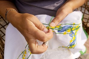 cross-stitch embroidering by woman