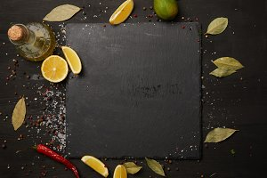 Dark slate board with spices and lem