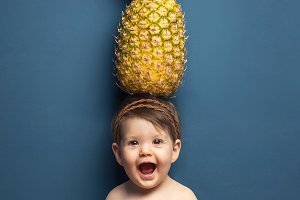 Baby girl holding pineapple in head