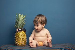 Happy baby girl play with pineapple