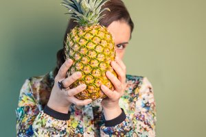 Woman holding pineapple over a face