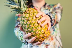Woman holding pineapple in her hands