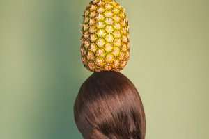 Woman holding pineapple over a head