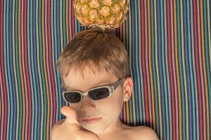 Happy child and pineapple sunbathing