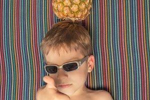 Happy child and pineapple sunbathing