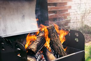 Fire over wooden logs in outdoors bb