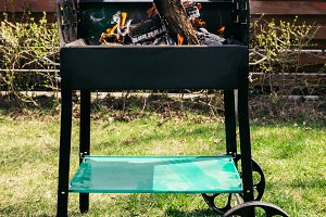 Metal outdoor grill with logs burnin
