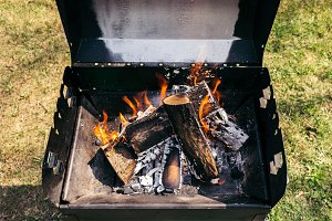 Outdoor grill with burning firewood