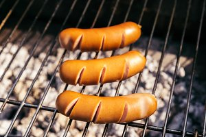 Hot sausages cooked outdoors on gril