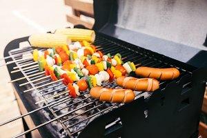 Sausages and vegetables on skewers c