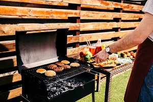 Man cooking grilled meat burgers for