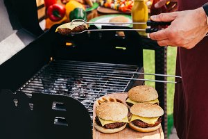 Man grilling meat for burgers on fir