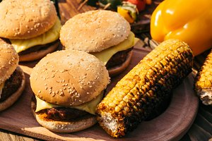 Burgers and corn cooked outdoors on