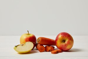 fresh carrots and apples on wooden s