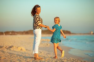 happy trendy mother and child on sea