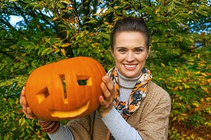 woman showing carved Halloween pumpk