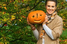 happy woman showing Halloween pumpki