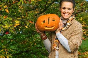 happy woman showing Halloween pumpki