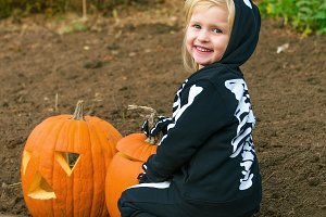 smiling child with Halloween pumpkin