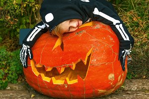 child hugging huge Halloween pumpkin