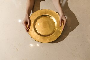 Golden metal plate in female hands o