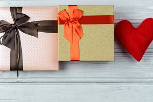 two gift boxes and a wooden heart on
