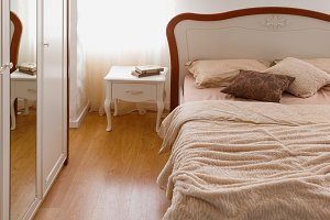 Light bedclothes on bed in cozy bedr