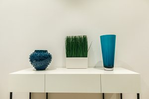 Blue vases and grass on white table