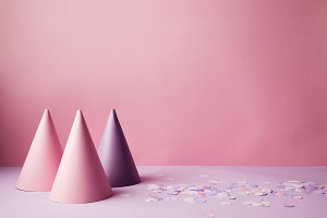pink and violet party hats and confe
