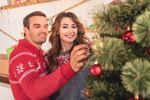 smiling couple in sweaters decoratin