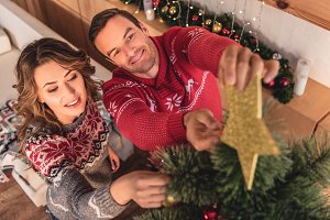 beautiful couple decorating christma