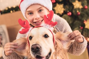 happy child in santa hat and dog wit